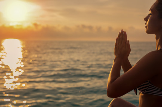 Beautiful young woman doing yoga on the beach at sunset