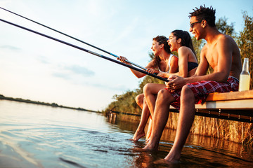 Group of friends sitting on pier by the lake and fishing.They joying in beautiful summer sunset.