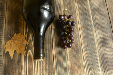 Autumn composition wine bottle grapes leaves on wooden background copy space