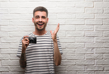 Young man holding vintage camera standing over white brick wall very happy and excited, winner expression celebrating victory screaming with big smile and raised hands
