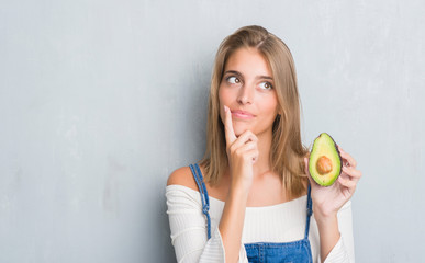 Beautiful young woman over grunge grey wall eating avocado serious face thinking about question, very confused idea