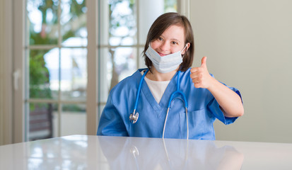 Down syndrome woman wearing nurse uniform happy with big smile doing ok sign, thumb up with fingers, excellent sign