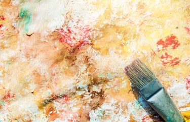 Composition of dirty painting brushes on colorful background