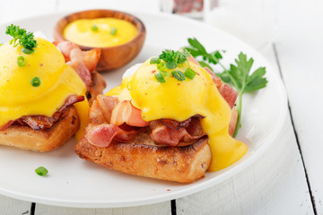 Eggs benedict with bacon on white  wooden background .