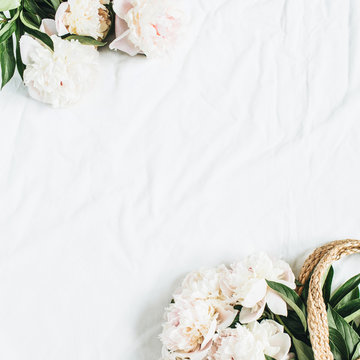 Straw bag with white peony flowers on white background. Flat lay, top view floral concept.
