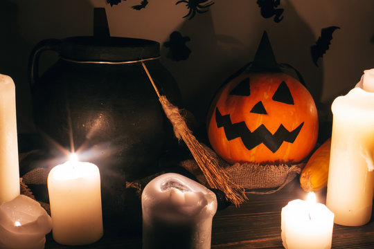 jack o lantern pumpkin with candles, bowl, witch broom and bats, ghosts on background in dark spooky room. Happy Halloween concept. fall halloween image