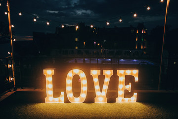 big white love letters in light bulbs for photo booth at wedding reception in night outdoors. love word lights, stylish evening decor for wedding ceremony