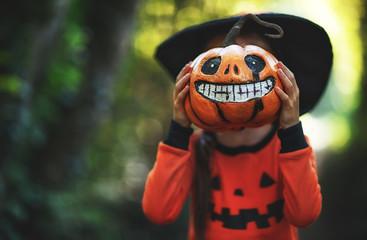 Happy Halloween! horrible creepy child girl in  pumpkin costume  in forest. Fototapete