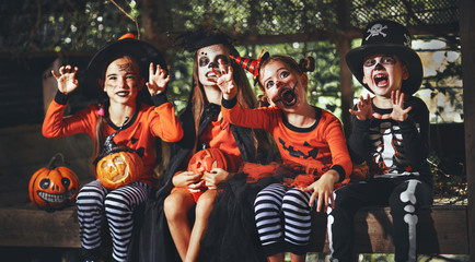 happy Halloween! a group of children in suits and with pumpkins in forest.