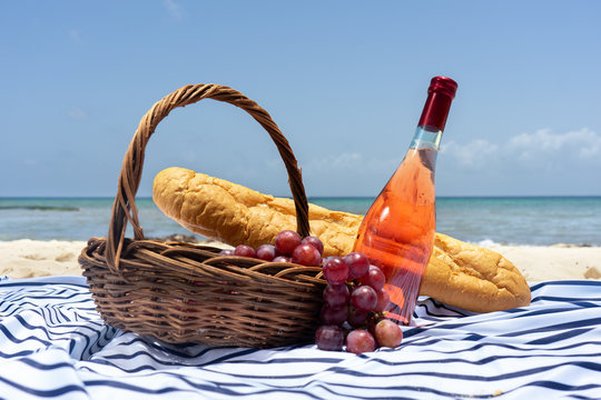 Beach picnic with wine, baguette bread and grapes