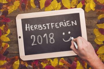 """Kreidetafel mit Aufschrift """"Herbstferien 2018"""" auf Holztisch mit herbstlicher Dekoration"""