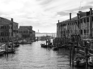 Monochrome image of the guidecca area of venice with boats moored next to historic old buildings