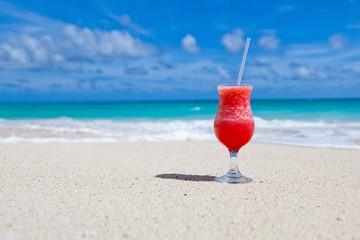 Red cocktail mocktail with straw on the sunny beach with waves