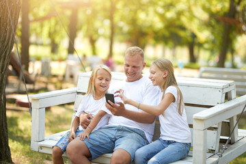 Family on the bench with phone