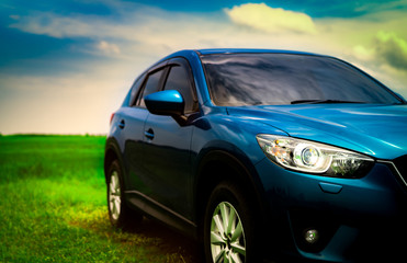 Front view of luxury blue compact SUV car with sport and modern design parked on green grass field with blue sky and white clouds. Hybrid auto and automotive. Road trip and car driving for travel.