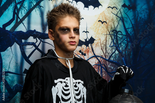 cute  young boy with black makeup in skeleton costume stands in front of dark background  sc 1 st  Fotolia.com & cute  young boy with black makeup in skeleton costume stands in ...