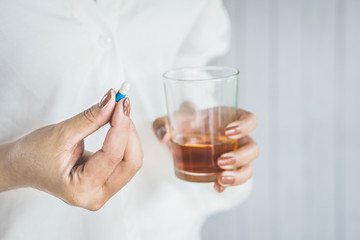 stress woman hand taking medicine with glass of alcohol, healthcare and medical concept background