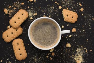 Café con galletas en mesa negra