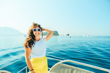 young pretty woman at boat nose sea with mountains and island on background