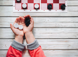 The child plays checkers. White and black checkers in children's hands. Children's school of board games.