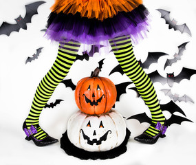 Funny green black Striped legs of a little girl with halloween costume of a witch with witch shoes and smiley halloween pumpkin jack o lantern