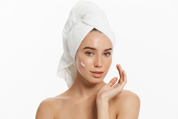 Close up beauty portrait of a smiling beautiful half naked woman with towel on her hair applying face cream isolated over white background.