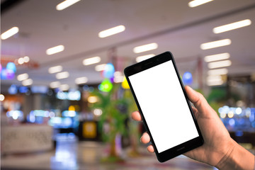 Woman hand holding mobile smart phone at shopping department store, blurred background, digital technology in concept.