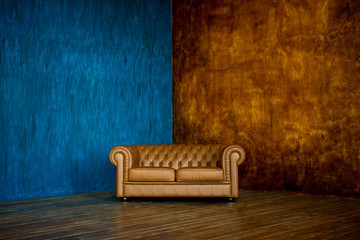 brown sofa chester on a background of blue and brown walls. Fotomurales