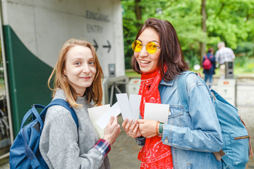 Two happy girls student at the entrance to zoo with tickets