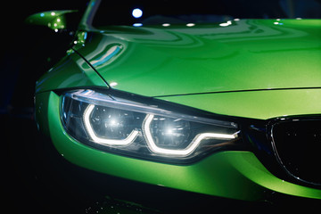 Closeup headlights of modern car during turn on light in night. Wall mural