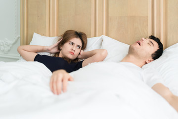 Annoyed Asian wife blocking her ears from noise of husband snoring in bedroom at home. Young couple have problem with man's snoring.