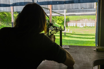 Girl shooting from rifle at shooting range