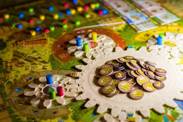 Colorful boardgame with cogwheels, figurines, chips and playing cards