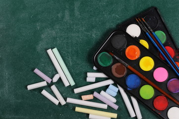 Chalks, paintbrushes and color palette on green chalkboard, blackboard, background and texture, top view