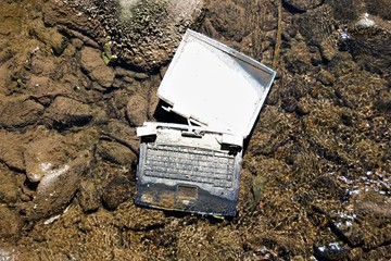 Laptop in the river /Carelessly discarded items pollute the environment and cause problems for all humanity