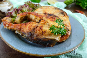 Large steaks of grilled fish with lettuce on a plate.