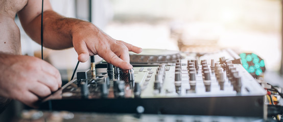 Closeup of DJ hands plays music on player and mixer
