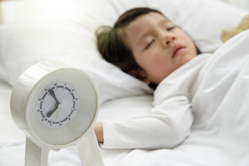 Child girl sleeping with alarm clock on the wooden bed in her bedroom, Happy asian child little girl and alarm clock wake up in the morning