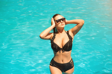 Elegant sexy woman in black bikini on the sun-tanned slim and shapely body is posing near the swimming pool. Amazing sexy girl takes a sunbath in the swimming pool. Big tits, large breasts, boobs.