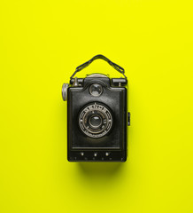 black old camera genos on green yellow background isolated from above