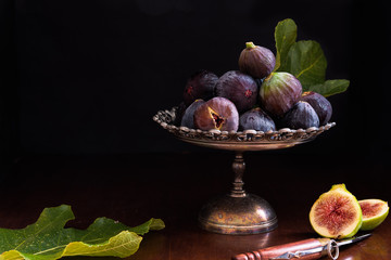 black and white figs on metal dish; still life with leaves and knife. Low key
