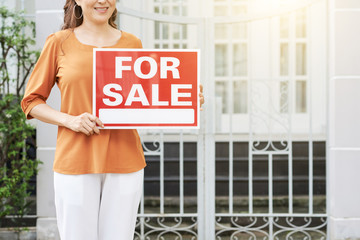 Cropped image of female real estate agent holding for sale sign
