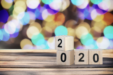 Wooden cube number 2020 on plank and abstract bokeh background, happy new year concept
