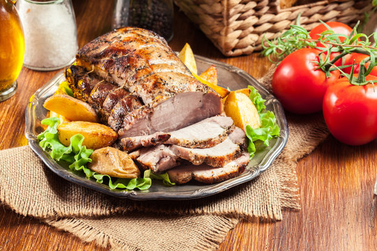 Roasted pork loin with baked potatoes and herbs