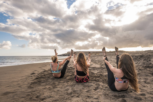 epic image with young nice women doing workout and pilates fitness exercises at the beach during an amazing sunset. enjoying lifestyle and tropical place for happy people