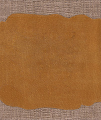 Piece of leather on the fabric textile texture background