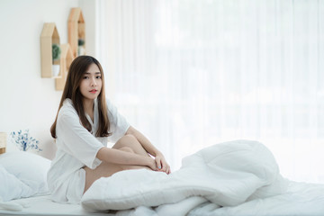Beautiful Asian lady resting on white bed. Cute women sitting in the bed her smile thinking about something.