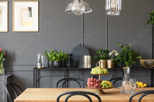 Lamps Above Wooden Table And Black Chairs In Grey Dining Room Interior With Poster Real