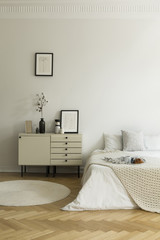 Monochromatic, white bedroom interior with a bed and a nightstand. Breakfast served on the bed. Real photo.