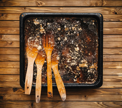 Wooden spatula in fat on a baking sheet. Dirty dishes. Festive dinner. Fat skillet with carbon. Dishwashing liquid. Advertising. Wooden spatula. Thanksgiving day.